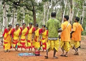 Santhal women and men perform tribal dance at the weekly market