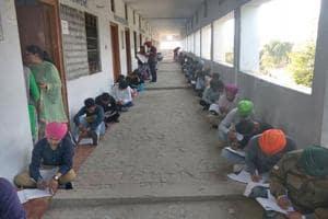 Students sitting on mats during their Class-12 PSEB exam at Government senior Secondary School, Talwandi Rai, Raiko on Wednesday.