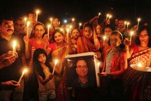 Residents take part in the candlelight vigil at Thane.