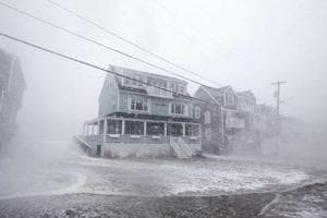 Waves crash over a house on Lighthouse Rd. as the road starts to flood during a large coastal storm on March 2, 2018 in Scituate, Massachusetts.