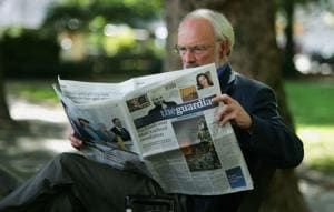 File photo of a man reading The Guardian newspaper in London.