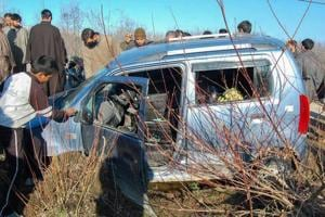 Locals stand around the vehicle that was hit during a shootout at Pahoo in Shopian district of south Kashmir on Monday.