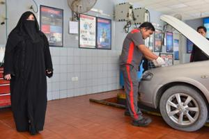 A picture taken on February 20, 2018 shows Saudi gas station supervisor Mervat Bukhari (L) standing near a worker at her workplace in Khobar, 400 kms east of Riyadh.