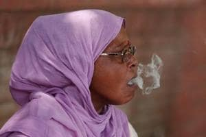 A woman smokes a beedi or a cigarette hand-rolled with tobacco leaf on a roadside in New Delhi.