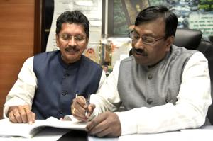 State finance minister Sudhir Mungantiwar and Minister of State for Home (Rural) Deepak Kesarkar scan a copy of budget that will be presented tomorrow.