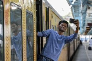 A man leans out of the Tejas train to snap a selfie at the CST in Mumbai, in May  2017.