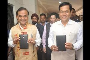 Assam chief minister Sarbananda Sonowal (right) and finance minister Himanta Biswa Sarma show the tablets containing the state's annual budget document, before presentation in the state assembly on Monday.