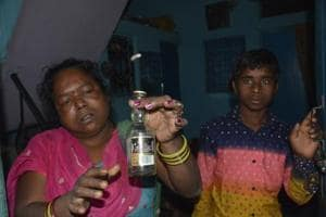A Khoda resident holds up a smuggled liquor bottle. Four persons of the colony died after consuming spurious liquor on Monday.
