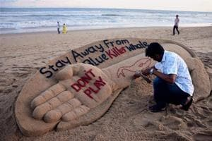 A file photo shows sand artist Sudarsan Pattnaik creating a sand sculpture warning against playing Blue Whale Challenge at Puri beach in Odisha.