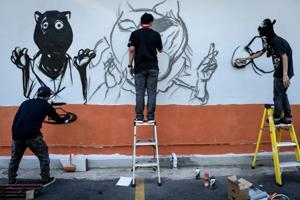 Thai graffiti artists paint murals of panthers at public places to...
