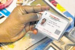 An Indian visitor gives a thumb impression to withdraw money from his bank account with his Aadhaar or Unique Identification (UID) card during a Digi Dhan Mela, held to promote digital payment, in Hyderabad on January 18, 2017. The Digi Dhan mela is a government initiative aimed at digital transformation in the country following the recent demonetization. / AFP PHOTO / Noah SEELAM