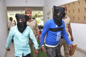 The two men in police custody on Monday. Police said they recovered ₹20,000 of the loot and a motorcycle.