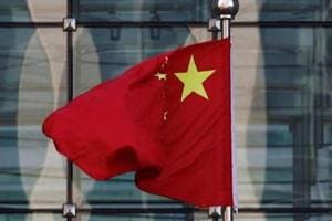 FILE PHOTO: A Chinese national flag flutters at the headquarters of a commercial bank on a financial street in central Beijing, China November 24, 2014.