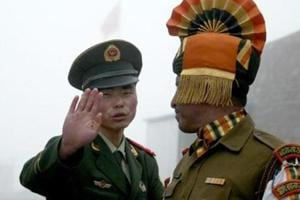 """A Chinese soldier gestures to an Indian soldier at a border crossing between India and China. India's envoy Gautam Bambawale in an interview to Hong Kong-based South China Morning Post had blamed China for the stand-off in Doklam saying it happened because Beijing tried to alter the """"status quo"""" which it should not have."""