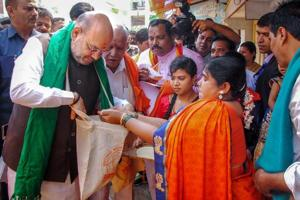 BJP president Amit Shah collects food grains from a farmer's family during a statewide door-to-door campaign ahead of Karnataka assembly elections at Doddabathi village in Davanagere on Tuesday.