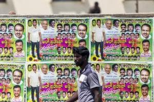 A pedestrian walks past election campaign posters for Karnataka elections 2018 in Bengaluru.