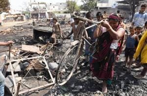 An elderly woman digs out charred cycle out of the ashes from the spot, where a fire broke out in the slum of Parameshwar Enclave Colony of Indira Nagar in Lucknow.