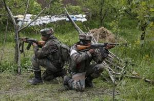 Soldiers take position inside an apple orchard during a search operation in Shopian on Thursday.