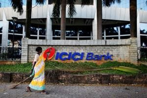 File photo of a municipal worker walking past a logo of ICICI Bank at its headquarters in Mumbai.