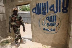A Nigerien soldier walks out of a house that residents say a Boko Haram militant had forcefully seized and occupied in Damasak.
