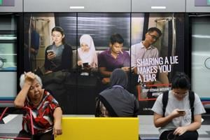 Commuters sit in front of an advertisement discouraging the dissemination of fake news, at a train station in Kuala Lumpur, Malaysia, on March 28.