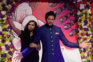 A visitor takes a selfie with a waxwork of Bollywood actor Shah Rukh Khan after it was unveiled at Madame Tussauds Delhi.