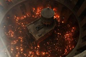 In pics:Thousands light 'holy fire' candles in Jerusalem church where...