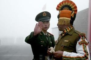 A Chinese soldier gestures to an Indian soldier at the Nathu La border crossing between India and China in Sikkim. Post resolution of the Doklam stand-off, the Chinese Peoples Liberation Army has replaced para-military Peoples Armed Police along the 3,488-kilometre long Line of Actual Control with troops doing training exercises.