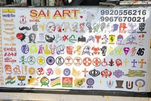 In GTB Nagar, the car-sticker shops (top) are papered over with logo samples.