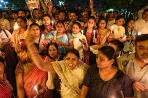 Congress women workers carry placards and shout slogans in protest against the rapes of minors in Kathua and Unnao, near India Gate in New Delhi on Thursday night.
