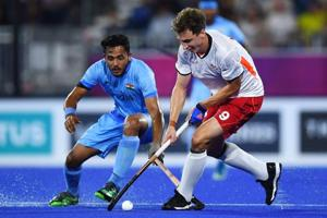 Harry Martin of England (R) vies for the ball with Indian men's hockey team