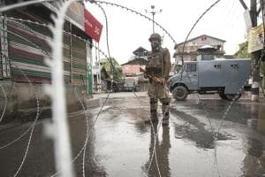 A soldier stands guard  in Srinagar during a shutdown. A resident of Moolu Chitragam, was abducted and fired upon from close range, injuring him severely on Sunday.