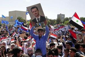 In this photo released by the Syrian official news agency SANA, protesters wave flags and portraits of President Bashar Assad, as they march during a demonstration to show solidarity with the Syrian armed forces, at Omayyad Square, in Damascus, Syria, Monday, April 16, 2018.