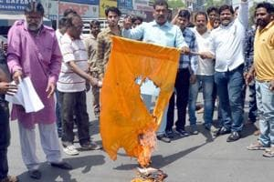 "Members of Dalit community burn a saffron flag purportedly symbolising the ""upper caste"" Hindu right wing — Shiv Sena factions and the Rashtriya Swayamsevak Sangh — at Shastri Chowk on Tuesday."