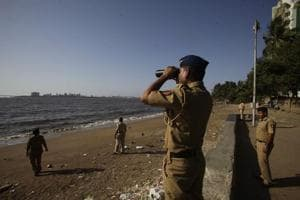 Policemen keep a close watch on the coastline of Mumbai City in Dadar area.