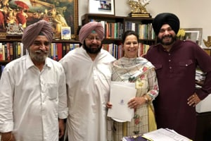 Punjab chief minister Amarinder Singh handed the appointment letter to Navjot Kaur Sidhu, who was accompanied by her husband Navjot Singh Sidhu (right)  and rural development minister Tript Rajinder Singh Bajwa (left), at his official residence .