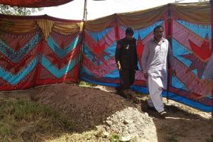 Pakistani policemen walk beside the grave of Italian national of Pakistani origin Sana Cheema, who was allegedly killed by her family members, in Gujrat of Pakistan