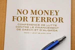 A program is seen before the start of a round table at a conference to discuss ways of cutting funding to groups including Islamic State and al-Qaeda, at the Organisation for Economic Co-operation and Development (OECD) headquarters in Paris on April 26.
