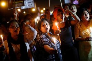 Women hold candles as they shout slogans during a protest against the alleged rape of a 10-year-old girl in Ghaziabad, in the outskirts of Delhi on April 25, 2018.