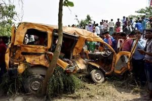 People gather around the mangled school van which collided with a moving train in Kushinagar on Thursday.