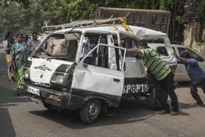 A mangled school van is being removed from the road after it collided with a tanker near Kanhaiya Nagar metro station in north-west Delhi.