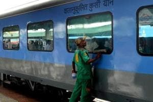 A railway worker cleans a coach prior to the trial run at New Delhi railway station.