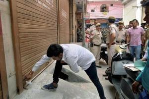 A municipal corporation official seals a shop at Gandhi Nagar during a sealing drive in east Delhi.