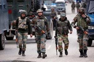 Army soldiers patrol a street near the site of a gunbattle between security forces and suspected militants in Khudwani village of south Kashmir