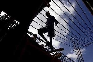 A labourer walks on an iron frame at the construction site of a residential complex on the outskirts of Kolkata, India.