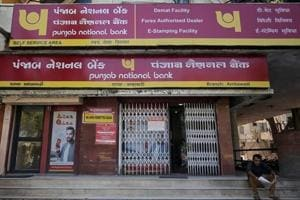 A man reads a newspaper outside a branch of Punjab National Bank in Ahmedabad.