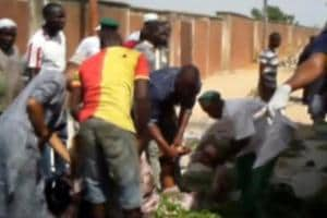 A still image taken from a video shot shows people helping an injured at the site of a blast attack in Mubi, Nigeria.