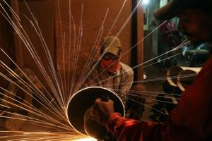 A worker cuts metal inside a workshop manufacturing metal pipes in Mumbai, India.