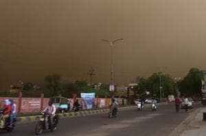 Vehicle ride past on a road during a dust storm in Bikaner on Wednesday.