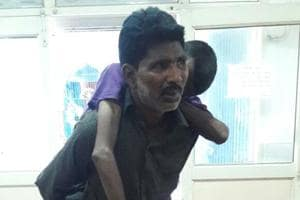 Pankaj carries the body of his brother on his back.